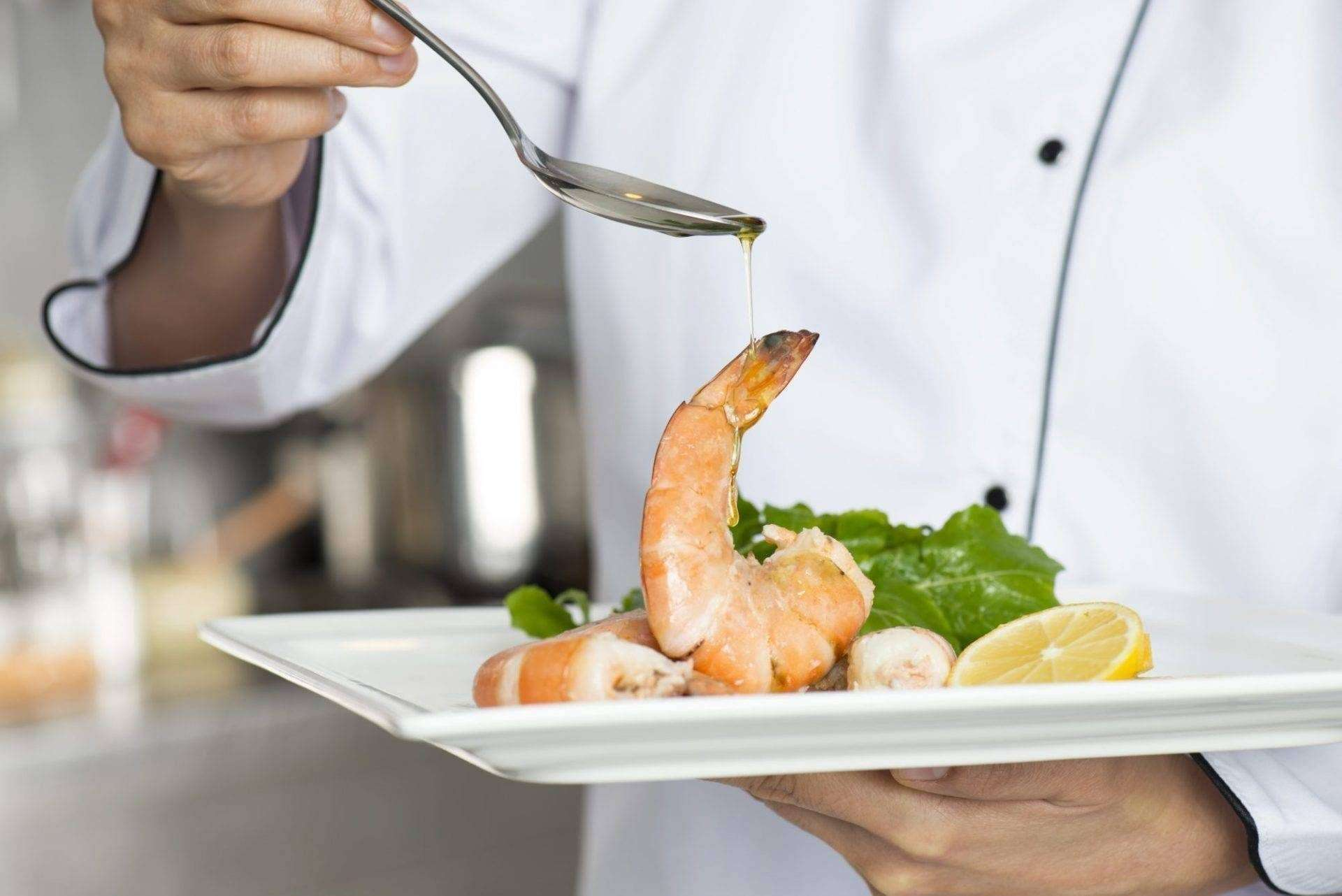 Chef completing shrimp plate.